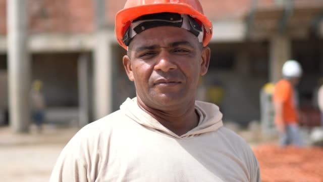 portrait of a construction worker in a construction site - etnia latino americana video stock e b–roll