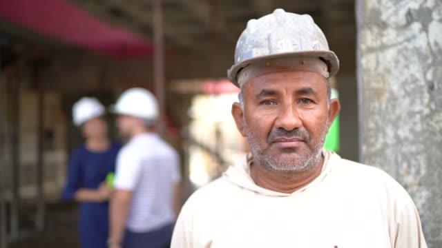 vídeos de stock, filmes e b-roll de retrato de um trabalhador da construção em um canteiro de obras - capacete equipamento