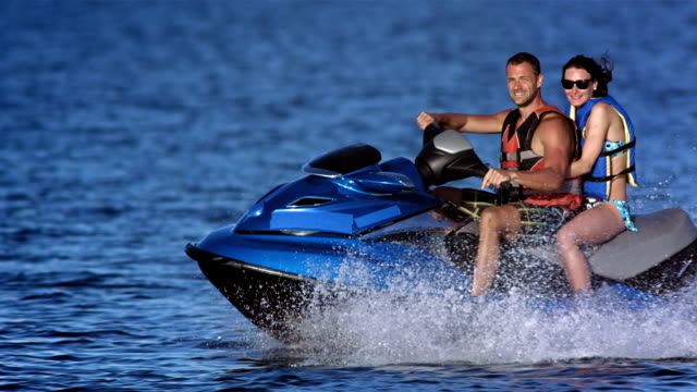 slo mo portrait of a couple riding jet boat - jet ski stock videos & royalty-free footage