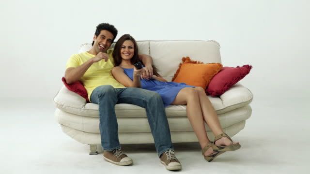 Portrait of a couple sitting on a couch and watching television