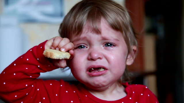 Portrait of a crying baby girl holding a dry bread