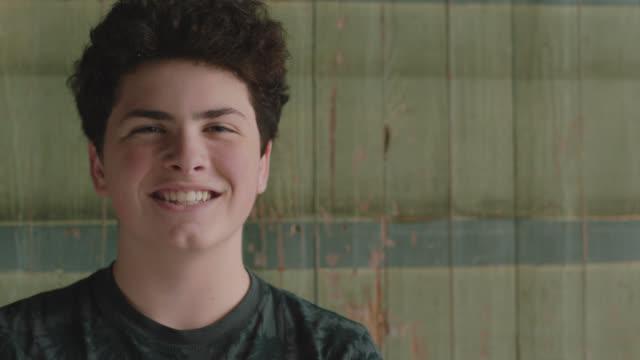 vídeos de stock e filmes b-roll de portrait of a curly haired teenage boy smiling into the camera - 14 15 anos