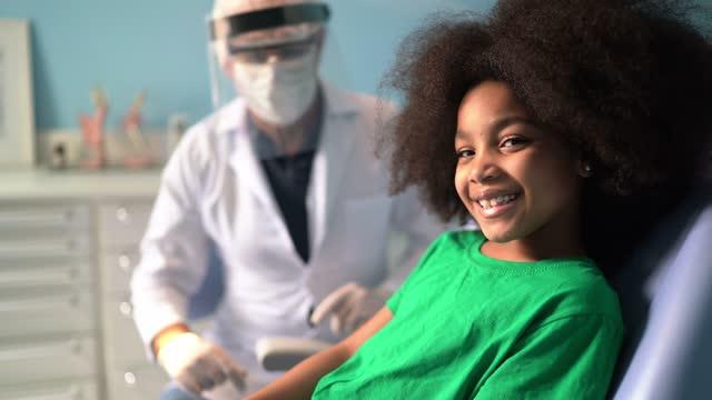 vídeos de stock, filmes e b-roll de retrato de uma menina bonita sentada na cadeira do dentista - clínica médica