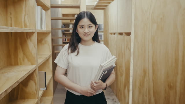 portrait of a cute young asian female student walking between book shelf (slow motion) - wide angle stock videos & royalty-free footage
