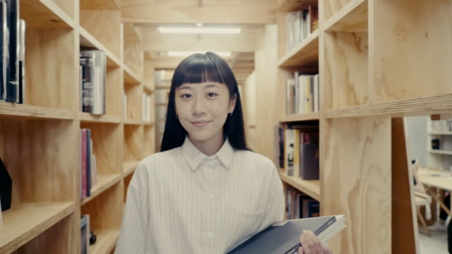 portrait of a cute young asian female student walking between book shelf (slow motion) - three quarter length stock videos & royalty-free footage