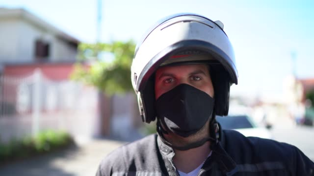 portrait of a delivery man with face mask at street - helmet stock videos & royalty-free footage