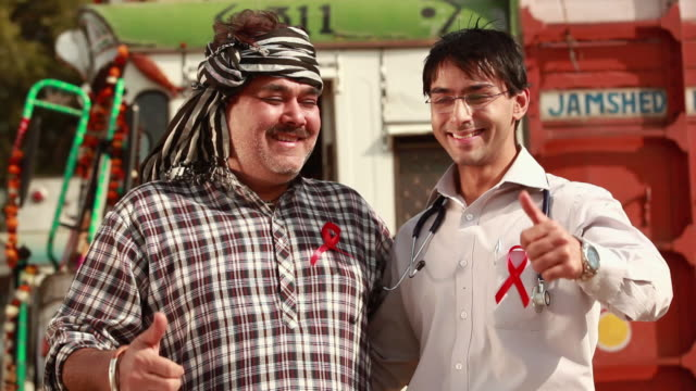 portrait of a doctor and a truck driver with aids ribbon on the chest giving thumbs up gesture, ballabgarh, haryana, india - wachsamkeit stock-videos und b-roll-filmmaterial