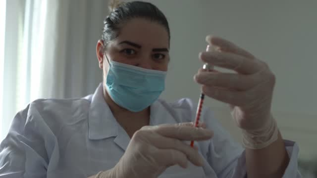 stockvideo's en b-roll-footage met portret van een arts die vaccin voorbereidt - het dragen van gezichtsmasker - trots