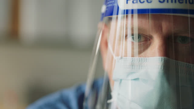 slo mo cu portrait of a doctor wearing a face shield and protective face mask - epidemiology stock videos & royalty-free footage
