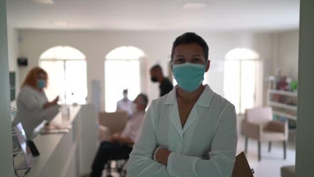 vídeos de stock, filmes e b-roll de retrato de um médico trabalhando em um hospital usando máscara facial - braços cruzados