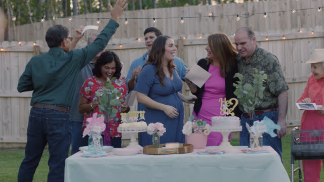 portrait of a family celebrating at a gender reveal party before finding out the gender - baby boys stock videos & royalty-free footage