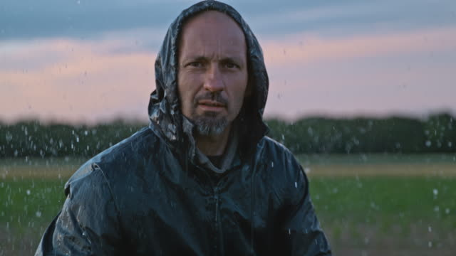 super slo mo portrait of a farmer on a field in the rain - rain stock videos & royalty-free footage