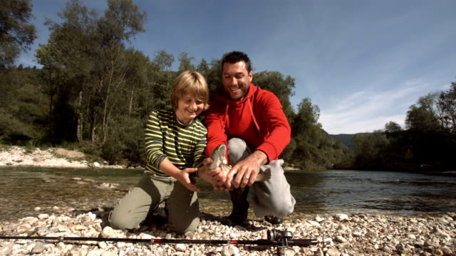hd: portrait of a father and son releasing the fish - recreational pursuit stock videos & royalty-free footage