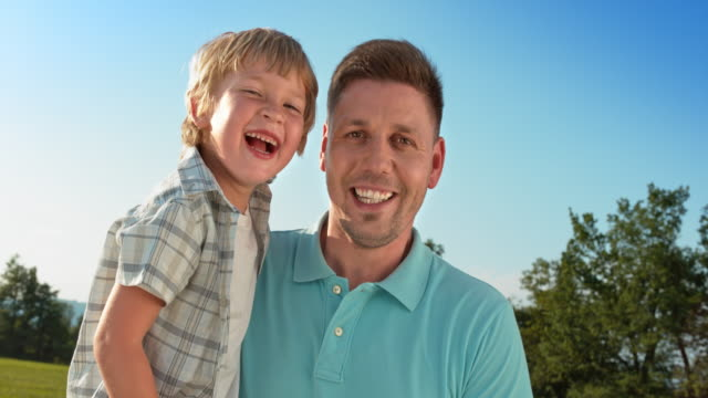 SLO MO Portrait of a father holding his son and smiling into the camera