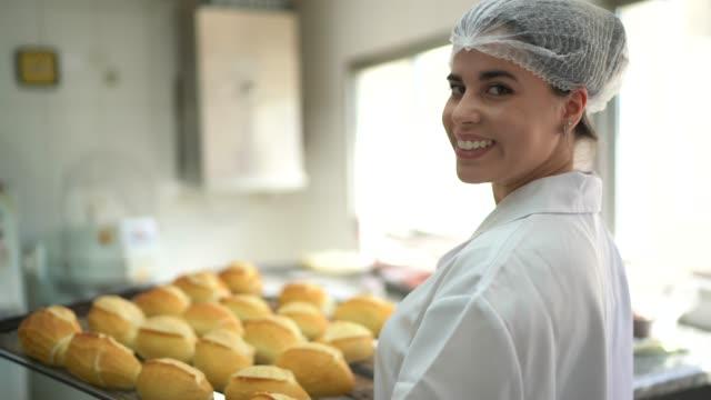 パンでいっぱいのトレイを持つ女性パン屋の肖像画 - オーブンの天板点の映像素材/bロール