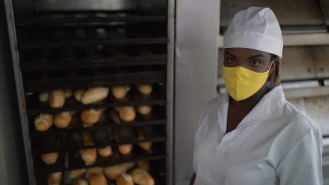 portrait of a female baker in front of a bread storage with face mask - loaf of bread stock videos & royalty-free footage