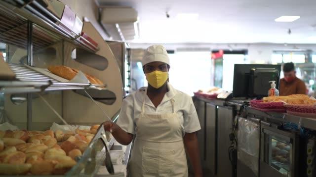 vídeos de stock, filmes e b-roll de retrato de uma padeira pegando pão com máscara facial - comida e bebida