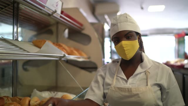 portrait of a female baker picking up bread with face mask - convenience stock videos & royalty-free footage
