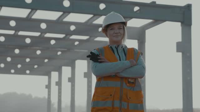 vidéos et rushes de slo mo portrait d'une entrepreneure en construction marchant sur le chantier le matin - bras croisés