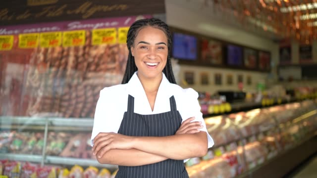 portrait of a female butcher standing with arms crossed in front of a butchers shop - raw food stock videos & royalty-free footage