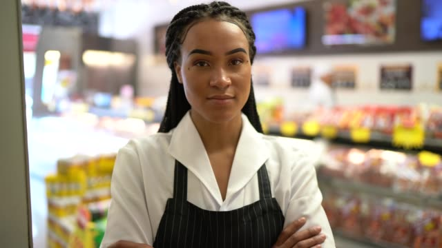 portrait of a female butcher standing with arms crossed in front of a butchers shop - butcher stock videos & royalty-free footage