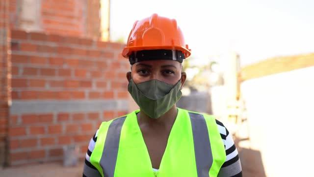 建設現場で保護フェイスマスクを使用した女性建設作業員の肖像画 - 土木技師点の映像素材/bロール