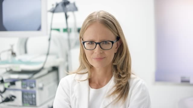 portrait of a female doctor in a white robe standing in her office and smiling - blond hair stock videos & royalty-free footage