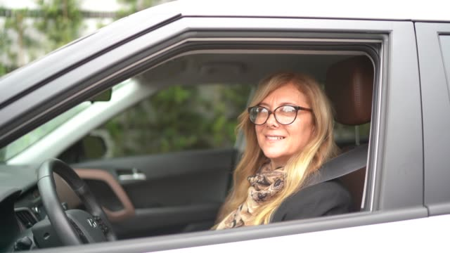 portrait of a female driver smiling inside a car - chauffeur stock videos and b-roll footage