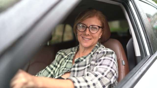 portrait of a female driver smiling inside a car - car rental stock videos and b-roll footage