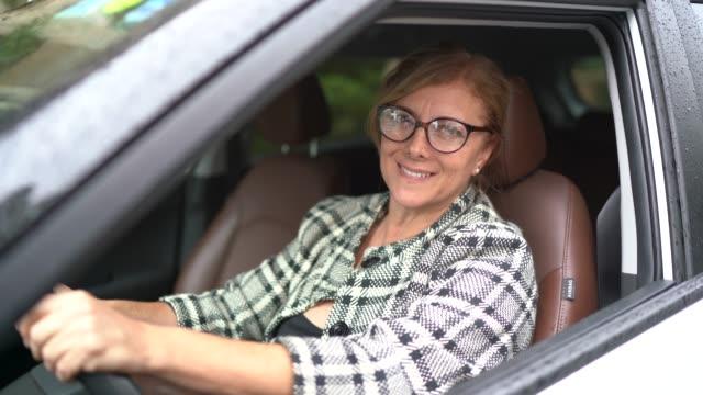vídeos de stock, filmes e b-roll de retrato de um excitador fêmea que sorri dentro de um carro - new