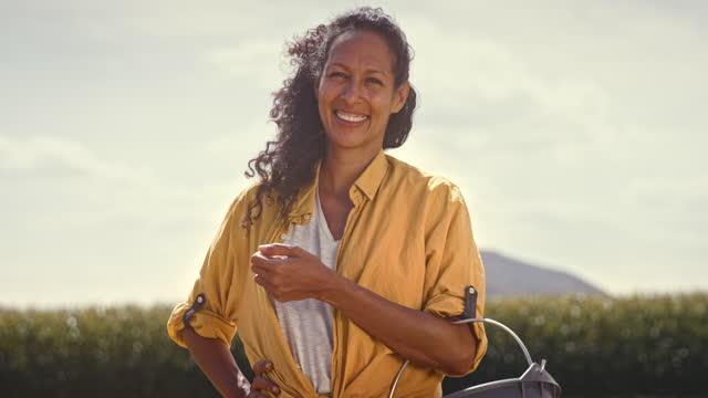 vidéos et rushes de slo mo portrait d'une agricultrice souriant tout en semant à la main au soleil - 40 44 ans