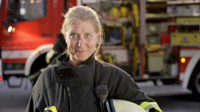portrait of a female firefighter taking off her helmet - potere femminile video stock e b–roll