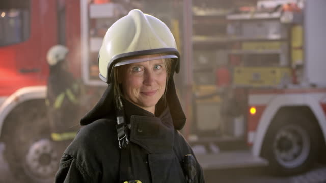 vídeos de stock e filmes b-roll de portrait of a female firefighter wearing a protective helmet - bombeiro