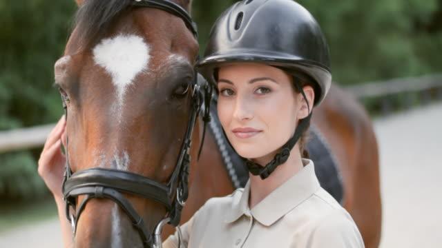 slo mo 雌ライダーでポーズを取るハーベイ馬 - 乗馬点の映像素材/bロール