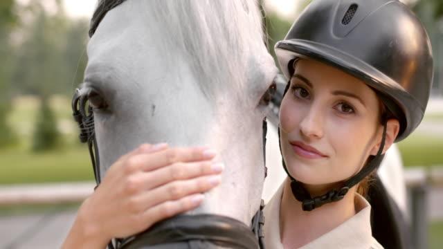 slo mo brunette donne fantino cavallo bianco sul naso stroking - casco protettivo da sport video stock e b–roll