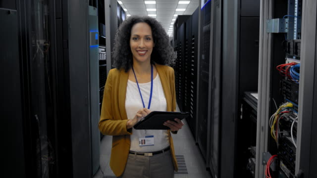 portrait of a female it engineer in the server room - tecnico video stock e b–roll
