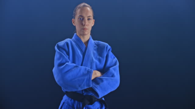 slo mo ds portrait of a female judoist in blue outfit on black background - world sports championship stock videos & royalty-free footage