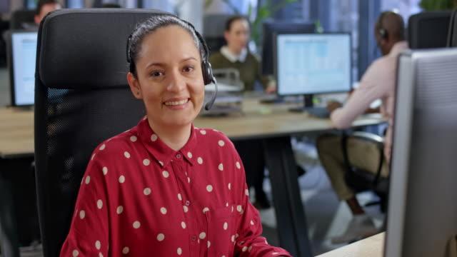 vídeos y material grabado en eventos de stock de retrato de una agente latinoamericana de call center sonriendo a la cámara - call center latin