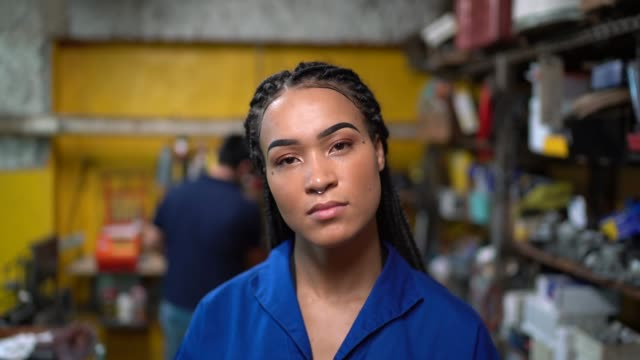 portrait of a female mechanic in a auto repair shop - incidental people stock videos & royalty-free footage