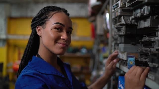 vídeos de stock, filmes e b-roll de retrato de um mecânico fêmea em uma auto loja de reparo - estrutura construída