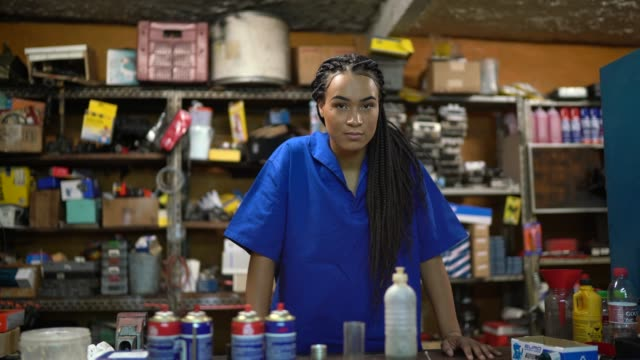 vídeos de stock e filmes b-roll de portrait of a female mechanic standing behind de counter in a auto repair shop - brazilian ethnicity