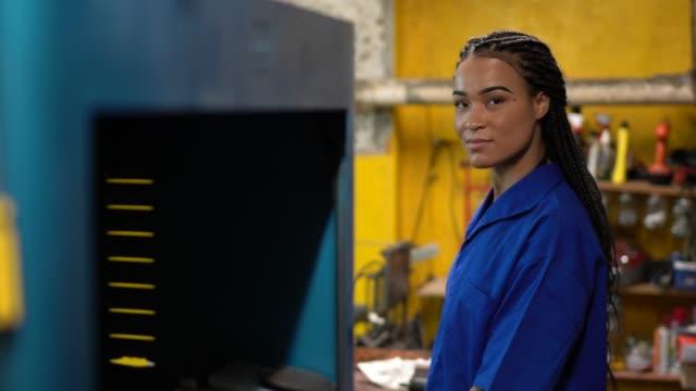 porträt einer mechanikerin mit gekreuzten armen in einer autowerkstatt - werkstatt stock-videos und b-roll-filmmaterial