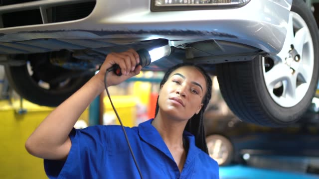 portrait of a female mechanic working standing under car holding a light bulb - stereotypically working class stock videos and b-roll footage