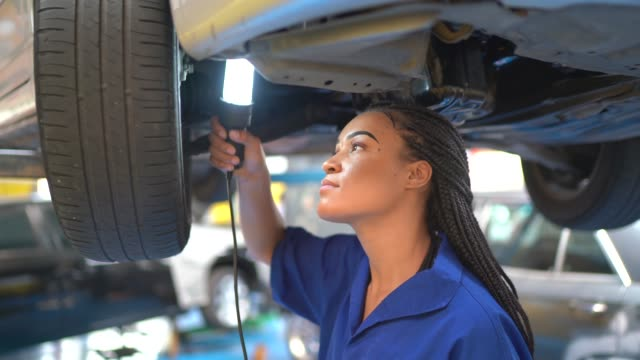 portrait of a female mechanic working standing under car holding a light bulb - technician stock videos & royalty-free footage