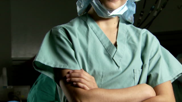 portrait of a female nurse in scrubs with arms crossed smiling - female nurse stock videos & royalty-free footage