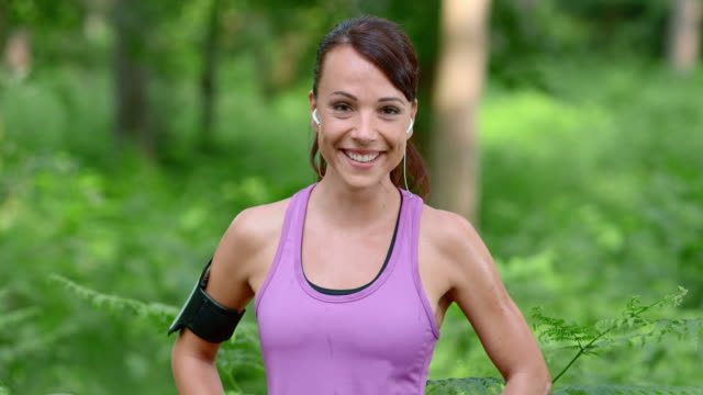slo mo ds portrait of a female runner smiling in the forest - purple stock videos & royalty-free footage