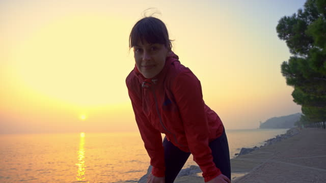 slo mo portrait of a female runner stopping on the footpath by the sea at sunrise - cardiovascular exercise stock videos & royalty-free footage