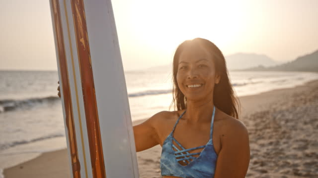 Portrait of a female surfer holding her surf board on the beach at sunset