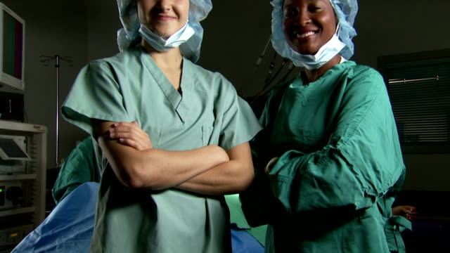 vidéos et rushes de portrait of a female surgeon and nurse in scrubs with arms crossed smiling - infirmière