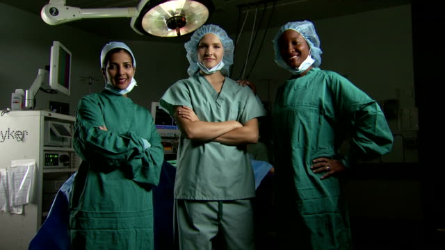 vídeos de stock e filmes b-roll de portrait of a female surgical team in scrubs with arms crossed smiling - enfermeira